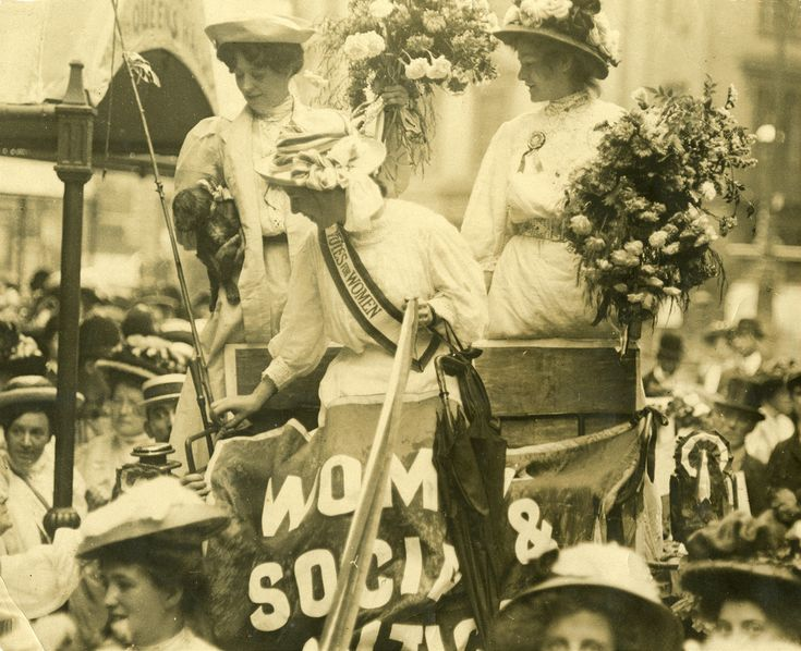 7JCC/O/02/044a Photograph, printed, paper, monochrome, Edith New and Mary Leigh each carrying a bunch of flowers, stepping down from a Women's Social & Political Union (WSPU) carriage outside the Queen's Hall; manuscript inscription on reverse 'Reception and breakfast at Queen's Hall London. To Hunger Strike Prisoners for Suffragette Movement 1908'. Part of the photograph has been cut away