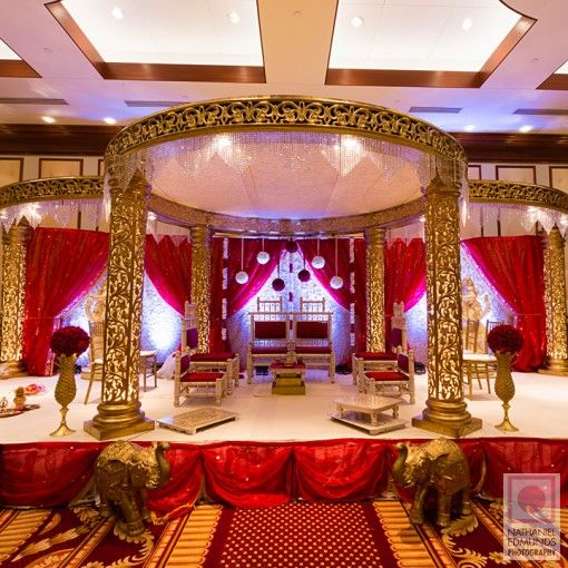 Gold circular pillar mandap with flower kissing balls via IndianWeddingSite.com