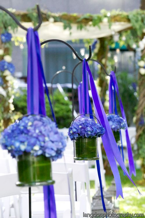 Shepard's hooks with blue ribbon and hydrangea in a leaf lined glass container line the aisle. Four Seasons wedding with Langdon Photography.