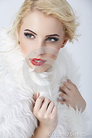Portrait of gorgeous stylish blonde woman posing in white fur against grey background.