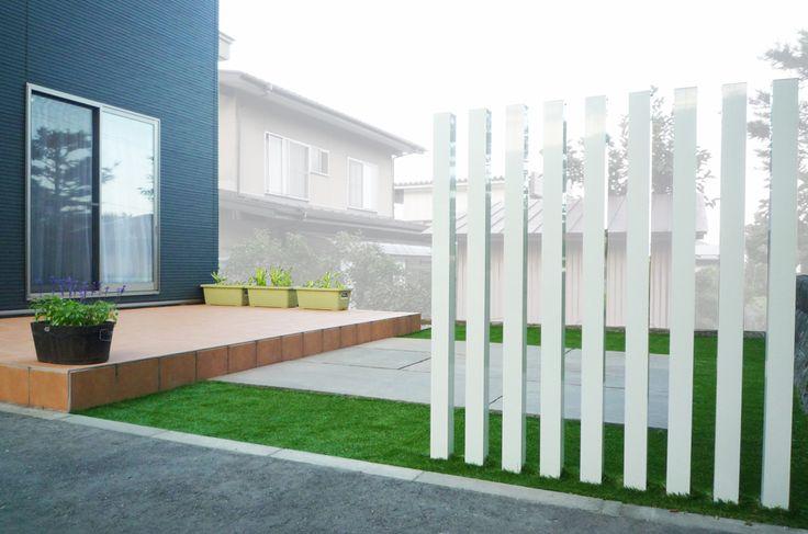 自然石と角柱の佇まいが際立つ、人工芝のシンプルなお庭。
