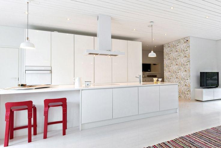 Kaapistoissa valkoiseksi maalatut kiiltävät mdf-ovet sormiurilla, jolloin vetimiä ei tarvita. Saarekkeeseen asennettu liesi, keittiöallas ja hana.