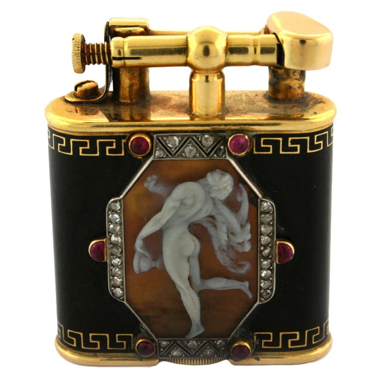 ALFRED DUNHILL. A Carved Shell Cameo Enamel Gold Lighter.  France  Circa 1930's  Centring on a cameo depicting a classical figure, within a border of rose-cut diamonds accented with cabochon rubies, the black enamel case embellished with a simple Greek frieze, signed Alfred Dunhill, Paris, Pat no. 143752 French assay marks, circa 1930