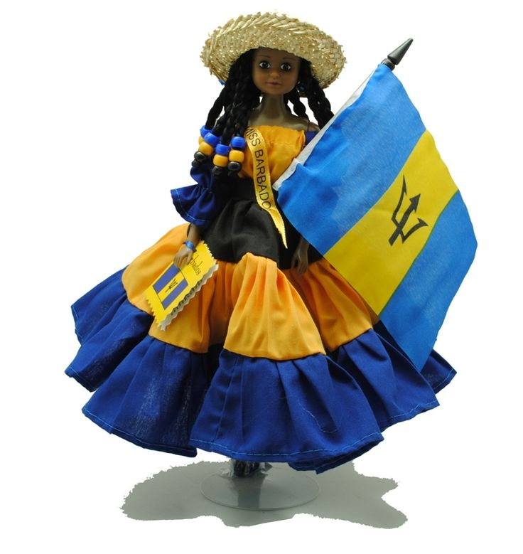 A patriotic decorative doll on a stand with hand made clothes in Barbados colours and carrying a Barbados flag.