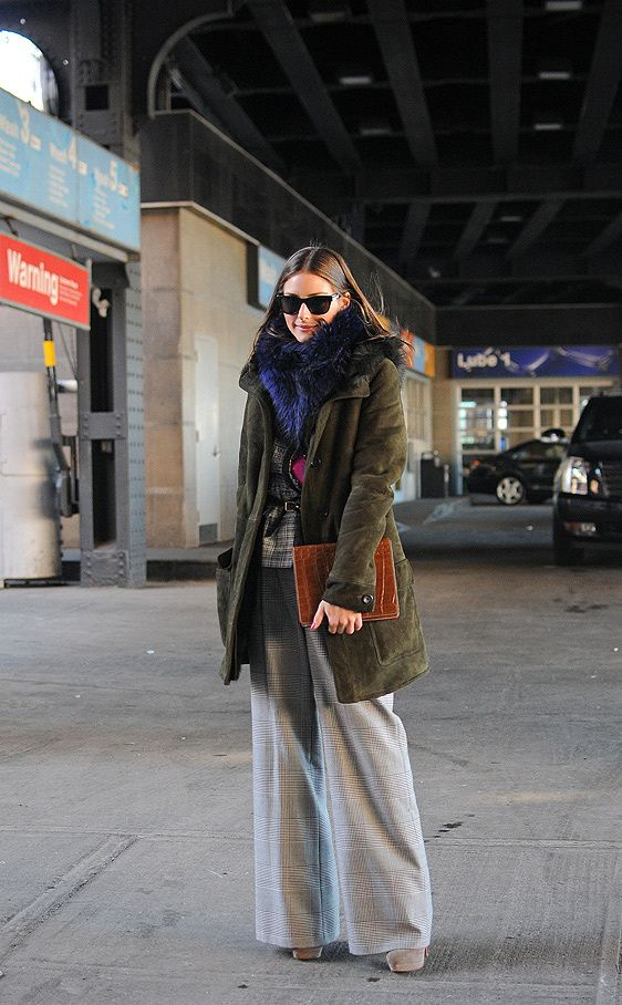 Olivia Palermo apuesta por un diseño de ante. Completa su outfit con unos pantalones en pata de elefante con estampado en príncipe de Gales.