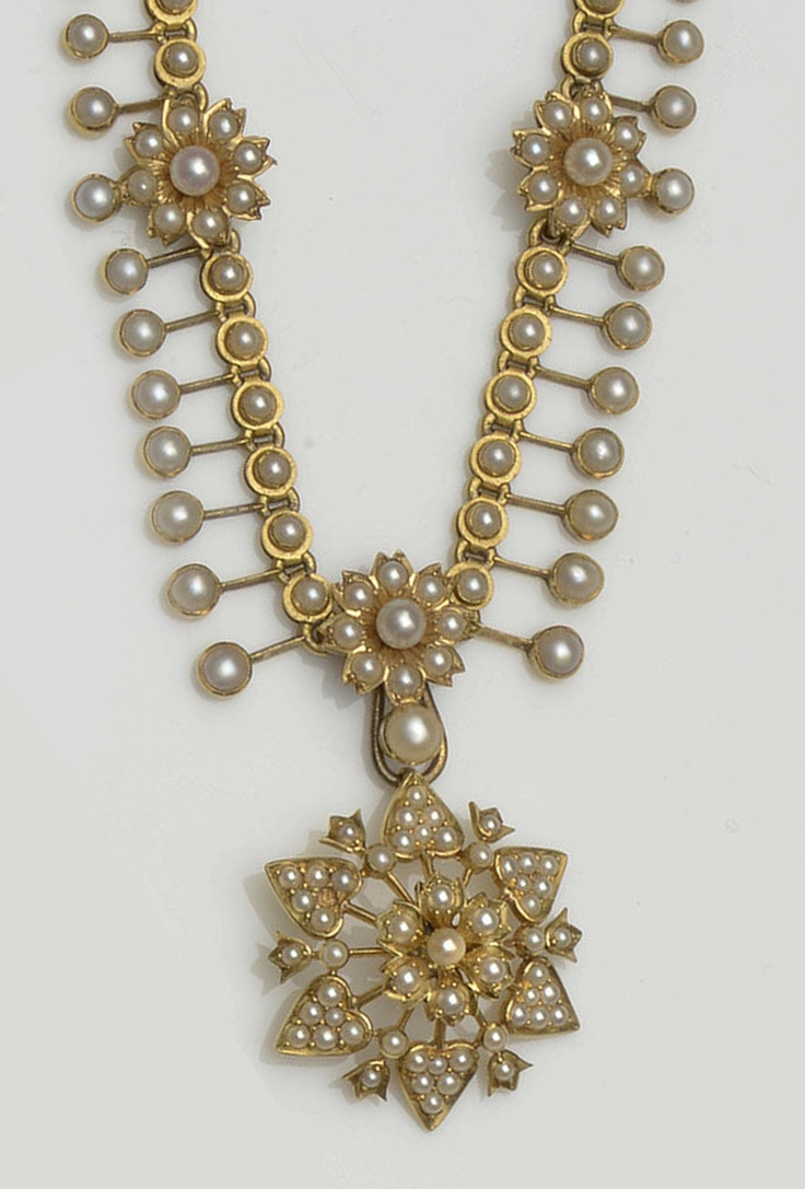 A late Victorian/Edwardian seed pearl fringe necklace The graduated fringe with three flowerhead accents, to a pearl set back chain, with a central detachable flower head drop, necklace length 40.5cm.