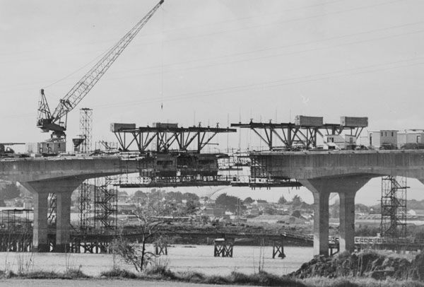 1980. 'The bridge over troubled water'. The third Mangere Bridge which had at the time of the photograph languished in an unfinished state for two years because of an industrial dispute. Photograph published in the Central Courier, 20 May 1980, South Auckland section, p. 1. Manukau Research Library, Courier collection, box 9/22. Footprints 00280.
