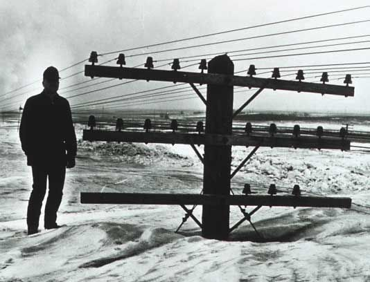 A man stands near a utility pole in North Dakota 9 March1966.  A spring blizzard produced snow so deep that it nearly buried the utility poles.