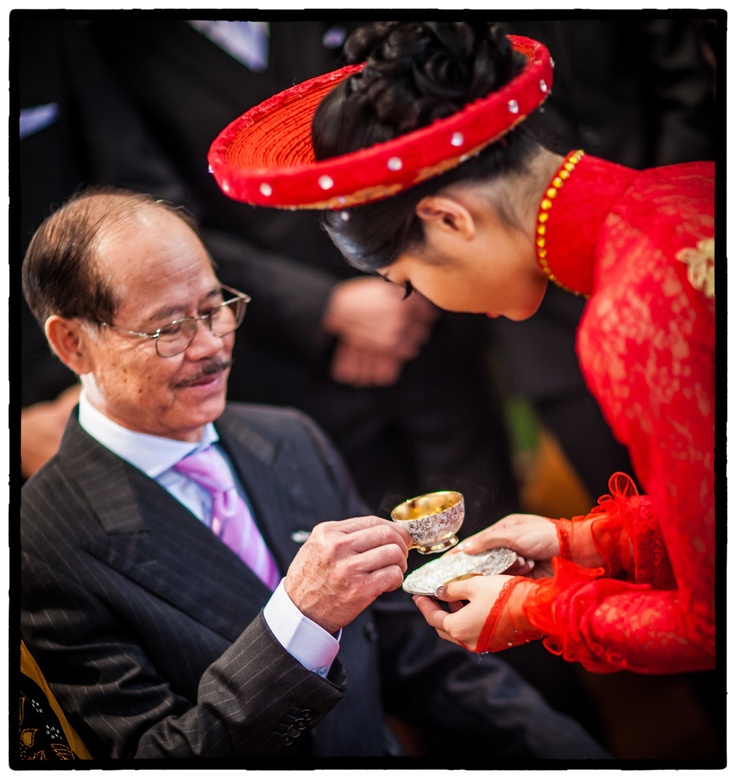 In time honoured tradition, the bride offers tea to her father as part of Vietnamese wedding ceremony