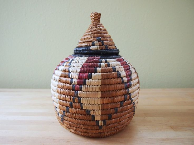 "African Zulu Beer Basket, Lidded Basket Woven in South Africa. This beer basket is a tightly woven, lidded basket crafted in South Africa and traditionally used to store the local brew. Each basket comes with a card explaining the patterning on the baskets and features the weaver's name. It's a beautiful art piece to add to your home. 6.5"" wide, 9"" tall."
