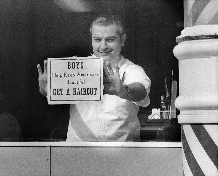 """#Emotions and #Storytelling """"Tagliatevi i capelli!""""  Il barbiere Carmine Filanova mostra un cartello nella vetrina del suo negozio a New York: """"Ragazzi, aiutate a mantenere l'America bella: tagliatevi i capelli"""". Filanova venne fotografato il 10 marzo del 1967, un periodo in cui andavano molto di moda i capelli lunghi. Per un taglio, disse Filanova, non ci sarebbe stato alcun sovrapprezzo, indipendentemente dalla lunghezza dei capelli. (AP Photo)"""