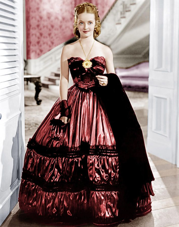 """Bette Davis in Jezebel, 1938. In the movie, she is going to the Olympus debutante ball.  She defiantly insists on wearing and flaunting herself in a """"saucy"""" and """"vulgar"""" red dress, customarily worn by a demi-mondaine - an """"infamous Vickers woman"""" - rather than the traditional virginal, pristine white gowns worn by unmarried women."""