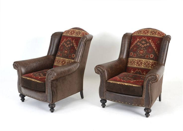 A wonderful pair of Old Hickory Tannery Southwestern wingback chairs, upholstered in a dark brown vinyl faux leather and Southwestern style chenille upholstered back and matching seat cushion with ...