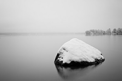 So serene is this picture with the snow on the rock in the lake.