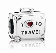 """The new Pandora sterling silver suitcase charm is engraved with the names of five continents: Africa; America; Asia; Australia and Europe on one side and inscribed with """"I ♥ To Travel"""" showcasing a translucent red enamel heart."""