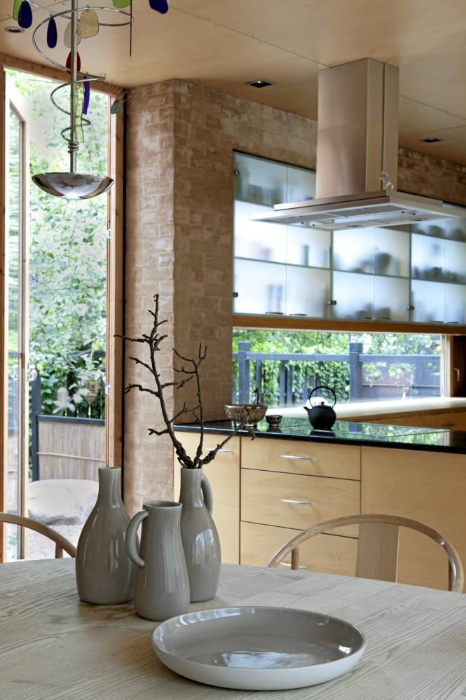 Det er lagt vekt på å lage skiller og åpninger til naturen. Kjøkkenskapene er gjennomskinnelige og ser derfor ut som en del av vinduet. Foran ser du glasert keramikk fra Kvist, og litt av Wegners Kina-stol. Bordet er spesiallaget til stolene.