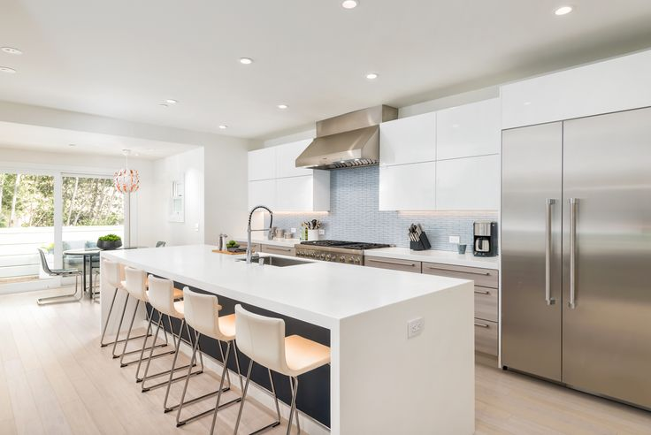 I love the long kitchen island, not only does it provide this galley kitchen with precious counter space, but it has plenty of seating for the whole family to chow down together. http://www.ybath.com/blog/modern-house-tour-a-new-day/