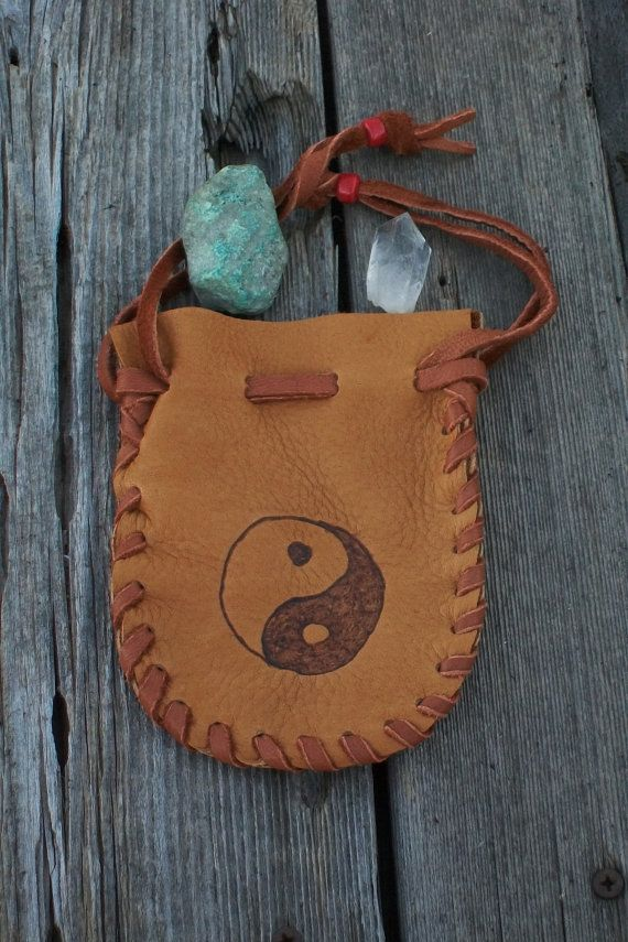 A soft leather pouch with a yin yang symbol made in saddle elkskin with rust lace. This pouch is approximately 5 inches tall and 4 inches wide double drawstrings and red crow beads. This little medicine bag is perfect for your crystals, amulet or anything small. Props are not included.