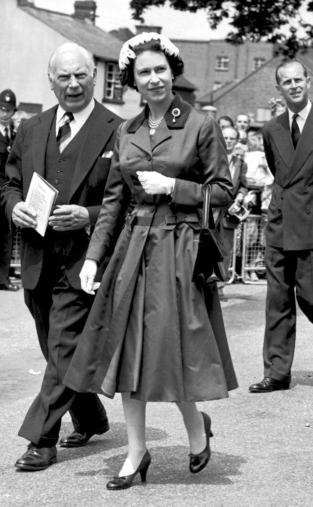 1958 from Queen Elizabeth II's Royal Style Through the Years  Queen Elizabeth wore a fitted trench coat in Crawley, England after attending the opening of Gatwick Airport with her husband Prince Phillip.