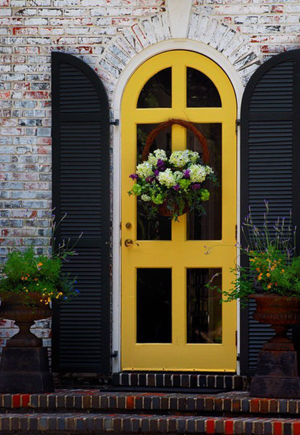 Love the yellow door offset by the black shutters. Check out the colorful brickwork!