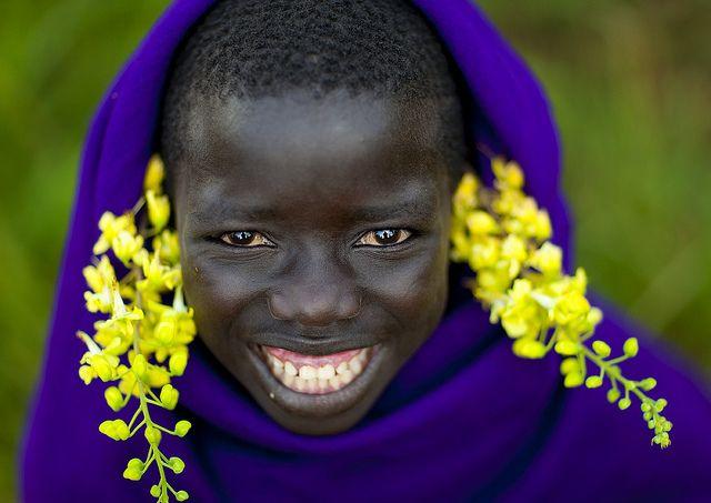 Surma smiling kid with flowers - Turgit Ethiopia by Eric Lafforgue, via Flickr