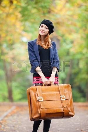 Рыжая девушка с чемоданом на осенней улице. photo