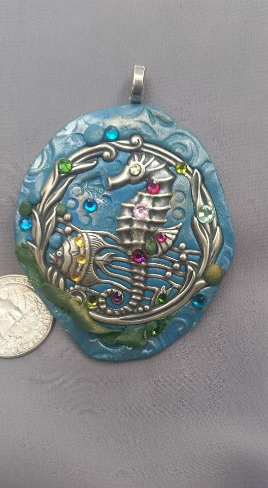 This is a oceanic/beachy pendant. The back is blue glazed Sculpey mixed with mica dust and imprinted with textures. The focal piece is a nickel metal stamping of a seahorse and a fish cruising through the green, gold-dusted seaweed. The images are enhanced with Swarovski crystals and beads.  I would recommend that this piece not be stored in or near high heat as the Sculpey can soften.  Please see image with American quarter for scale. $35.00