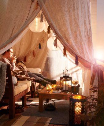 Ein Zelt im Beduinenstil auf einem Balkon mit SOLIG Netz in Weiß, darunter sitzt eine Person auf einer Couch, die für den Außengebrauch geeignet ist, und trinkt Tee.