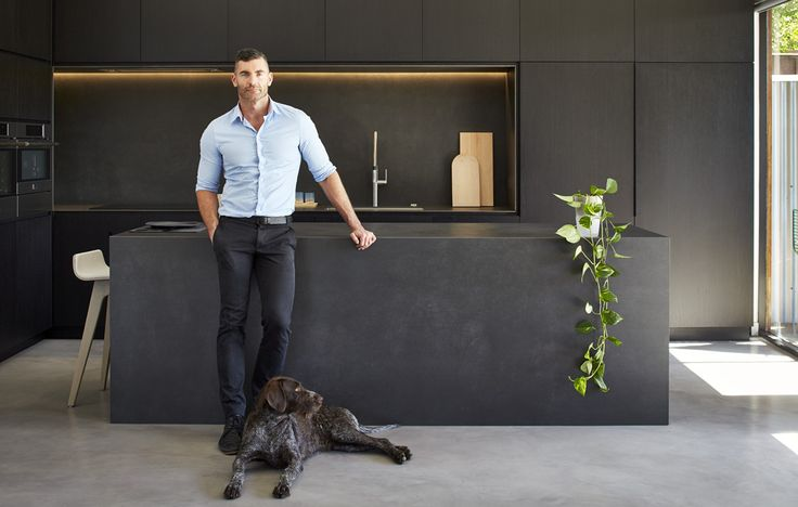 Matte black cupboards with timber bench but white tiled splash back and hardwood timber floors