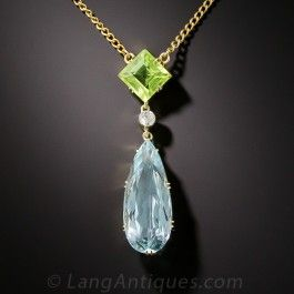 Blue sky meets green earth in this strikingly beautiful, colorful, and unusual combination of gemstones. An elongated pear shape aquamarine, with a deep pastel blue hue, is joined by a sparkling white diamond to a deep lime green square-cut peridot, all set in 15ct, gold (hence of British origin), with a touch of platinum to accentuate the diamond. This uniquely stunning Edwardian era jewel measures 1 1 /2 inches and suspends from an 18 inch chain. Dreamy!