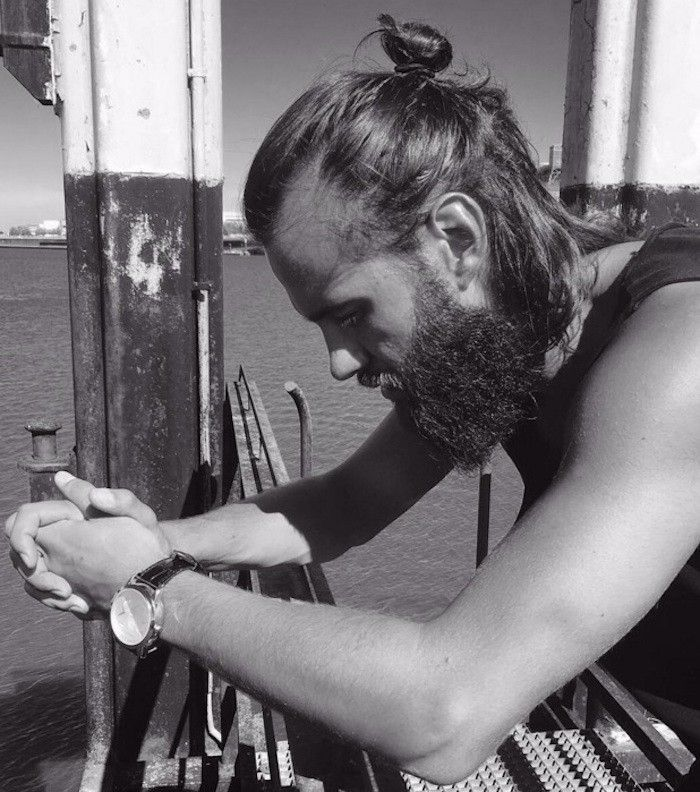 medium length hairstyles, bearded man leaning on railing, looking down and to the side, hair tied in man bun