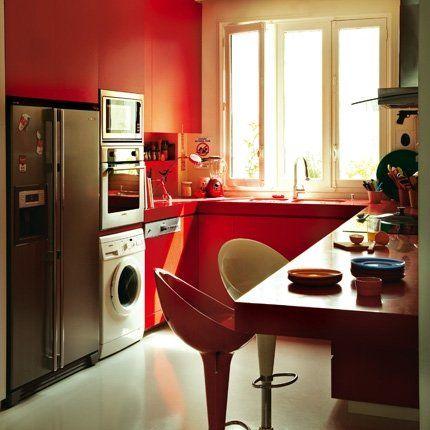 Cuisine rouge vif avec plan de travail, frigo en inox et électroménager encastré
