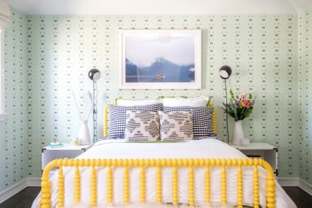 To enliven the white walls, designer Dee Murphy styled one side of this eclectic girl's room with sage-green wallpaper.A yellow bed frame and colorful area rug further the fun, energetic design, while a desk and chair leave room for studying.
