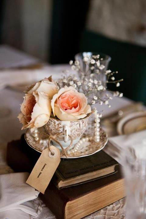 Teacup centrepiece using vintage books and handmade tags - I set up and styled these centrepieces for my own vintage wedding in March 2012...