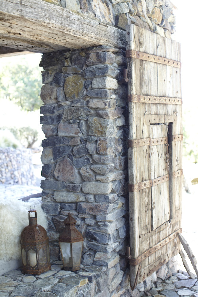 Texture: The textures of the door, rock wall, and the lanterns have rough surfaces and solid.