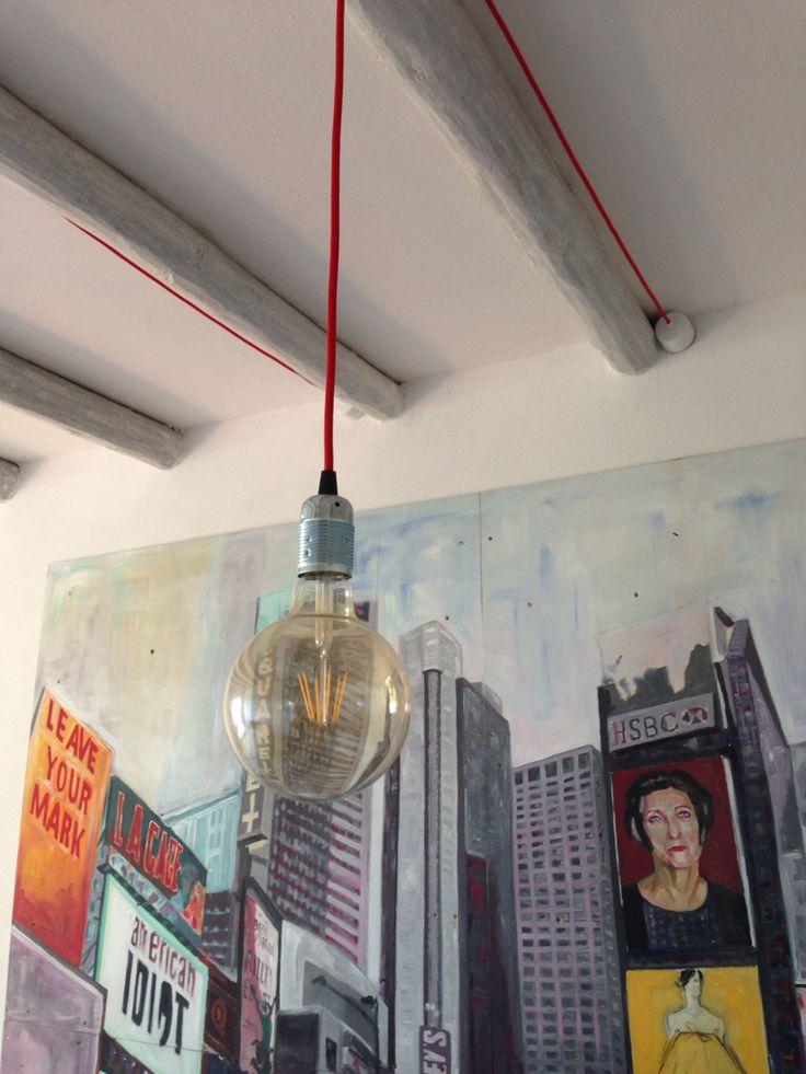 Illuminazione tavolo da pranzo con lampadine vintage. Lampadina a sfera, cavo in tessuto rosso e rosone in acciaio bianco.