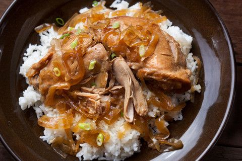 Slow Cooker Chicken Adobo: 4 medium yellow onions, halved and thinly sliced; 4 medium garlic cloves, smashed and peeled; 1 (5-inch) piece fresh ginger, cut into 1-inch pieces; 1 bay leaf; 3 lbs bone-in, skin-on chicken thighs; 3/4 cup soy sauce; 1/4 cup rice vinegar; 1 T granulated sugar; 1/2 tsp freshly ground black pepper. Steamed rice, for serving.