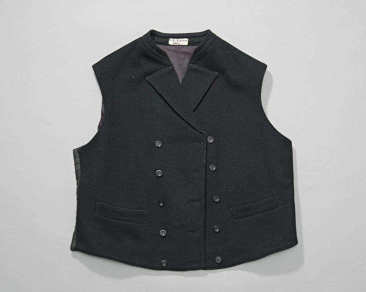 Double-breasted mannenvest van zwarte wol met rugpand van zwarte keperkatoen. Het vest heeft een klein opstaand halsboordje en hoog sluitend revers. Axel #Axel