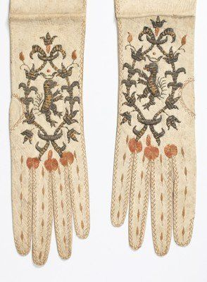 A pair of women's gloves, circa 1680-90, of white kid, elbow length, the fingers with decoratively stitched edges, pink pom-poms to the knuckles.