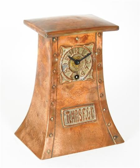 SCOTTISH SCHOOL COPPER MANTEL CLOCK, CIRCA 1910 with embossed silvered dial, the tapering body with riveted angles and plaque bearing inscription 'Tempus Fugit' , 24cm high
