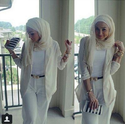 Hijabi in white and cream with dark belt and loose blazer, striped clutch purse