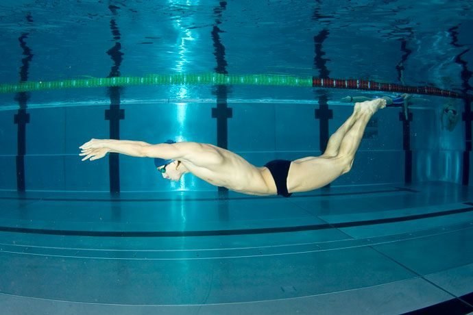 Swimmer practicing the wave-like movements of the butterfly stroke under water