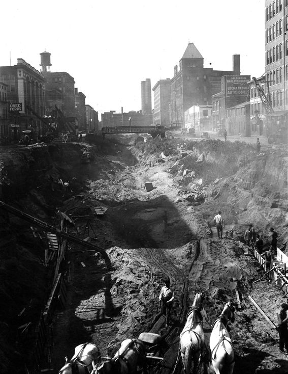 Cincinnati, Ohio, from the collection of the Public Library of Cincinnati and Hamilton County: October, 1920, excavation of the Miami-Erie Canal in Over the Rhine to make way for subway tunnel; Strobridge Lithographing Company in background.