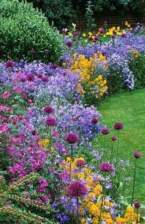 Note pompom style perennials for stability and texture in the design of this overflowing border