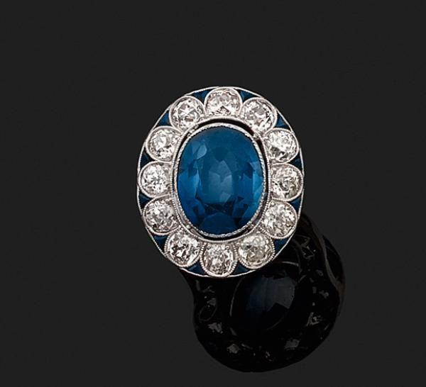 Belle BAGUE « marguerite » en or gris (750 millièmes) serti d'un saphir ovale entouré de diamants taille ancienne et saphirs calibrés.  Dim. du motif : 2,2 x 1,9 cm. Doigt : 54. Poids brut : 5,1 g.  Estimation 4.000/4.200€