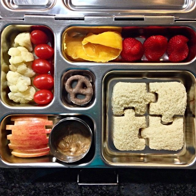 Today's lunch: Cream cheese + raspberry preserves puzzle sandwich, strawberries, dried mango, grape tomatoes, steamed cauliflower, apple + almond butter, and chocolate-covered pretzel. #PlanetBox #schoollunch #kidslunch #toddlerlunch #bento #lunchbox