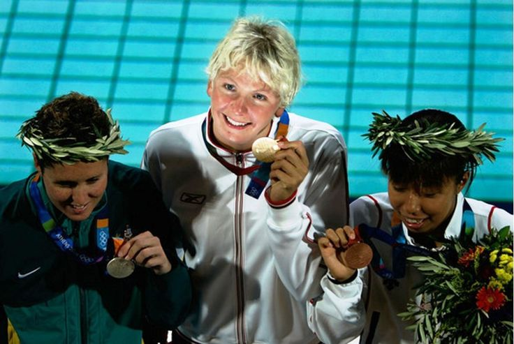 Gold medallist Otylia Jedrzejczak of Poland, silver medalist Petria Thomas of Australia (L) and bronze medalist Yuko Nakanishi of Japan (R) celebrate on the podium during the medal ceremony of the women's swimming 200 metre butterfly event on August 18, 2004 during the Athens 2004 Summer Olympic Games at the Main Pool of the Olympic Sports Complex Aquatic Centre in Athens, Greece.