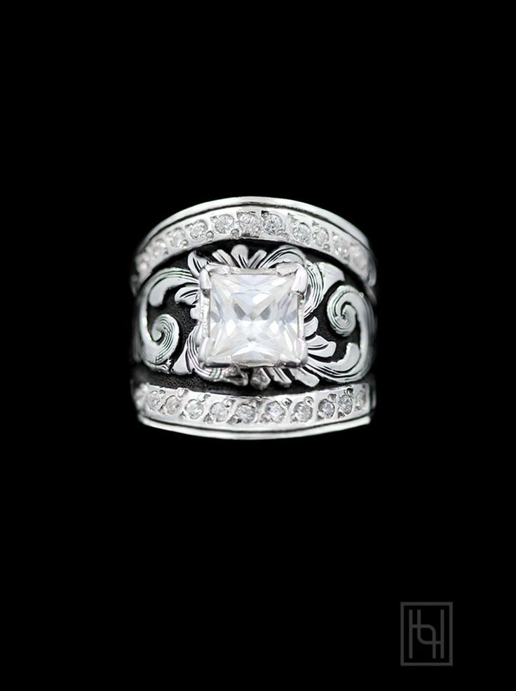 Enjoy cool silver tones and a western charm withthe Sterling & Crystal Statement Solitaire Ring.  Sterling Silver with a Square 7 mm Crystal Clear Cubic ZirconiaSolitaire andAccentsOxidized Silver Background.  Front Band Width: 7/8 in. Back Band Width: 3/8 in.