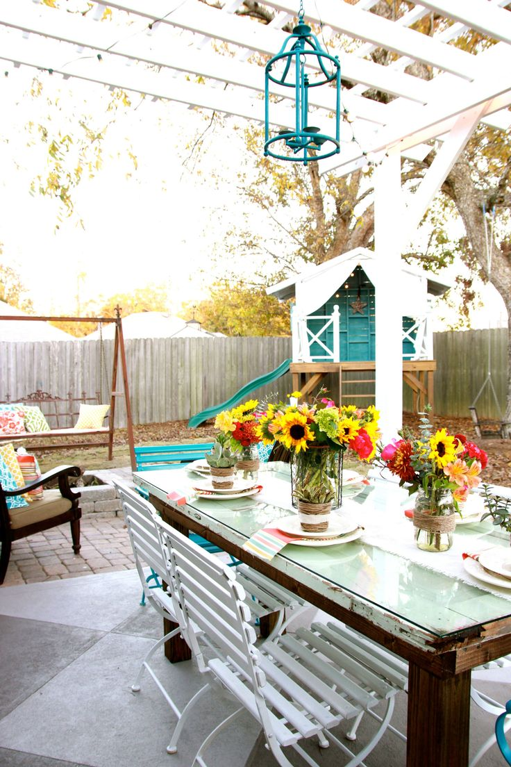 """While the back porch is a space for adults and kids alike, the Mills created a """"handmade hideaway"""" tucked back in corner of the yard just for their three kids. Complete with a pitched tin roof, wooden deck, and wave slide, the lofted fort is a kids' paradise."""