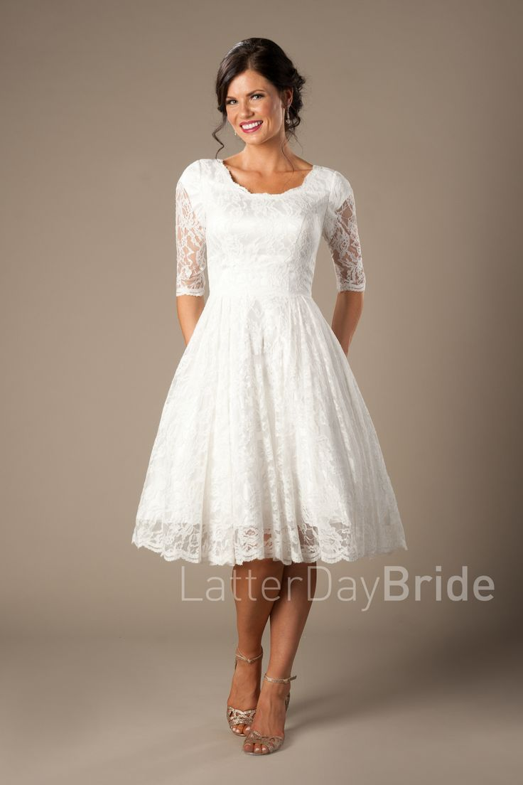 Quinn | Modest Wedding Dress | LatterDayBride & Prom | SLC | Utah | Worldwide Shipping | Wedding Dress under $500 | Budget | This lovely modest tea-length dress features a darling lace, beautiful illusion lace elbow-length sleeves and finished with a scalloped edging.     Gown available in Ivory or White     *Pictured in Ivory    Sleeve length or neckline can be customized.
